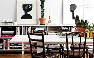 Eclectic apartment dining area with a sideboard filled eith books and cactus plants in terracotta pots