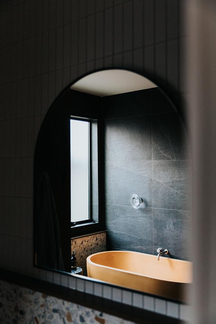 The colour of the statement bathtub pops against a deep, moody colour scheme.