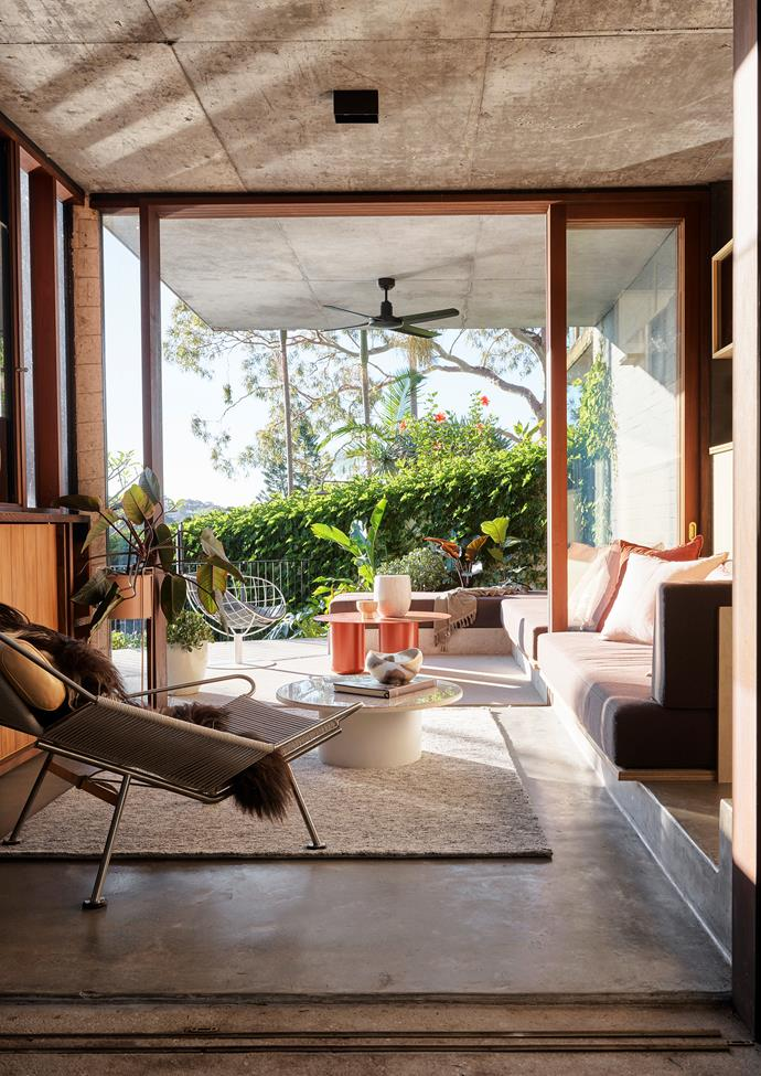 In the casual living zone that overlooks the pool, the built-in sofa with upholstery by Atelier Furniture extends from inside out to link the two spaces. Coco Flip 'Sequence' red table from Cult. 'Flag Halyard' chair by Hans J. Wegner. 'Plateau' coffee table from Blu Dot.