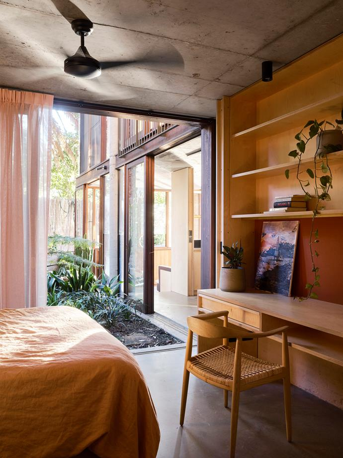 The ground-floor bedroom opens up to the palm-filled courtyard. The character of the original ceiling contrasts with the newly inserted joinery wall. Artwork by Anna Royal.
