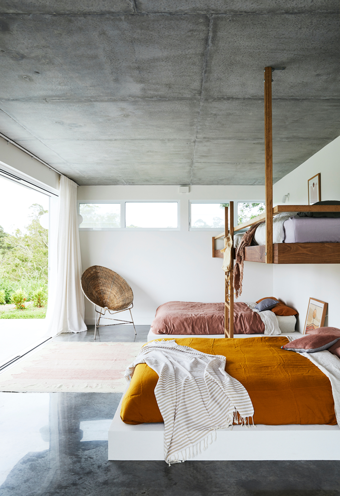 """Textured linen bedding in earthy tones bring warmth to this bedroom in a [sunlit Byron Bay home](https://www.homestolove.com.au/new-build-byron-bay-hinterland-22186