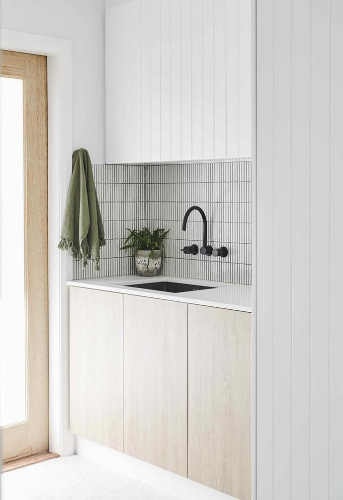 """An Inax finger tile splashback from Artedomus complements the black tapware from Astra Walker in the laundry of this [designer's home in Burleigh Heads](https://www.homestolove.com.au/creative-coastal-home-burleigh-heads-19542 target=""""_blank""""), NSW."""