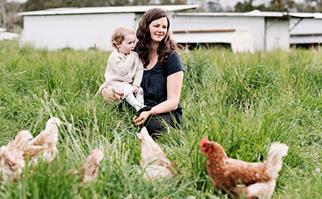 Woman holding child on farm surrounded by chickens