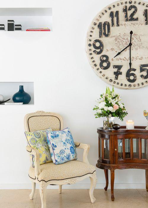One of a pair of antique Louis XV chairs in the hallway and the side table came from Margaux's grandfather. An oversized clock from Earthborn completes the vignette.