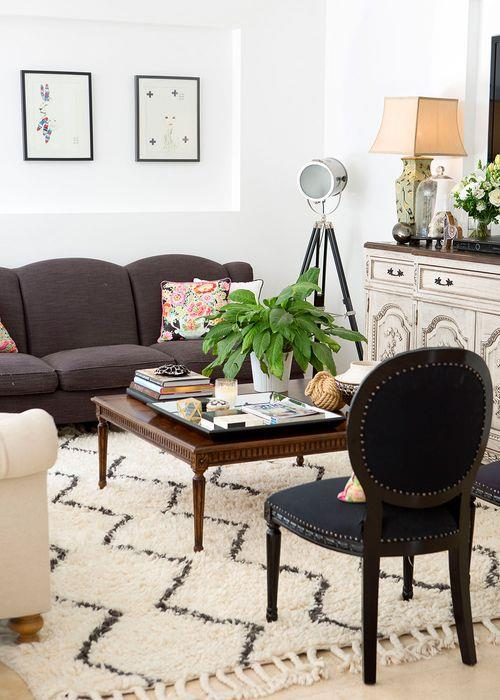 Corey and Margaux's living area is as chic as it is comfortable. The pair sourced the hand-carved Louis XVI sideboard and the parquetry-top coffee table from European Design, and the charcoal sofa from Far Pavilions. Margaux spotted this 'Souk' rug at West Elm. The couple commissioned Colleen Jaftha of One Sonny Day to create the embossed portraits of the children.
