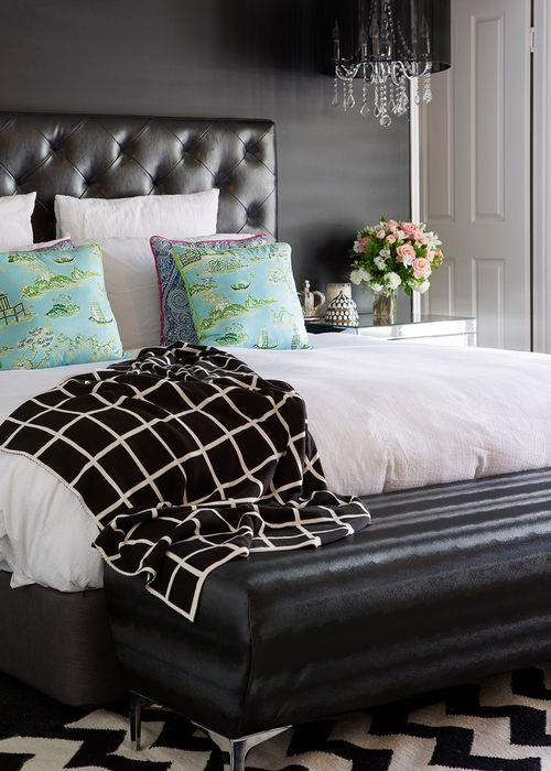 """A dramatic feature wall in Taubmans 'All Black' forms a backdrop to a stylish leather bedhead from Snooze, and allows the white bedlinen to pop. """"I keep my linen white because it makes it easier to change things up with cushions and throws,"""" says Margaux."""