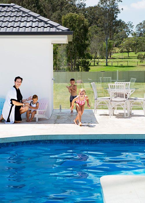 """All the home's spaces open out to the pool area, where Wylei and Memphis love to cool off. """"Having the pool so close to everything was a big selling point,"""" says Margaux, pictured with Jagger. For a sense of continuity, the same practical travertine flooring has been used here as inside the house, albeit in different finishes. Margaux found the 'Cape Cod' kids' chairs at Aldi."""