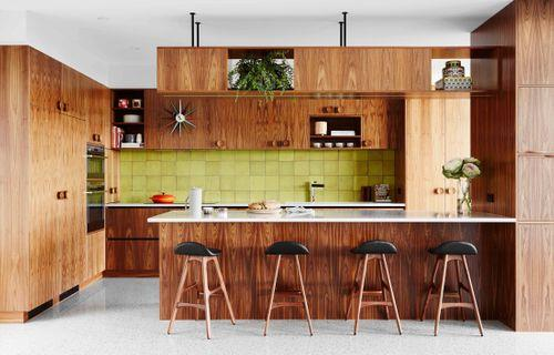 """Modern practicality prevails in the kitchen despite it being a loving ode to retro style. An array of storage comes courtesy of American walnut cabinetry by Acclaim Kitchens & Cabinets. """"I love the timber bulkhead above the island bench,"""" says owner. """"I wanted something a little left-of-centre – and it provides added storage."""" The apple-green splashback tiles from Academy Tiles were a serendipitous find by Jane during a trip to Melbourne. """"I had this exact colour tile in mind and walked up and down [the suburb of] Richmond before I saw these,"""" she says. """"As soon as I did, I said, 'This is it!'"""" The mother-of-two loves the low-maintenance appeal of the Silestone benchtops in Lagoon, while a cluster of leather-and-walnut Erik Buch replica bar stools from Life Interiors is a magnet at mealtime."""