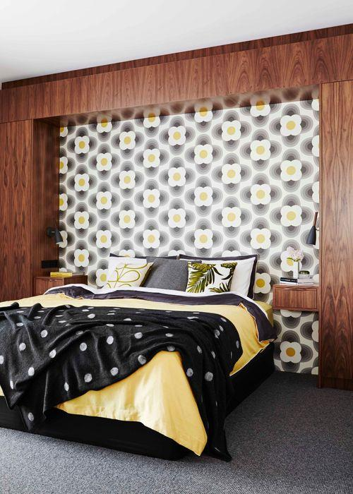 """""""Drew wasn't scared away by this floral wallpaper!"""" says owner, of the Orla Kiely 'Striped Petal' wallpaper in 110402 Graphite. """"The way it complements the American walnut cabinetry is my favourite part of this room."""" A 'Colonel Mustard' quilt cover set from Hunting For George continues the infusion of colour, while the flooring is Hycraft's 'Ravine' wool carpet in Pewter."""