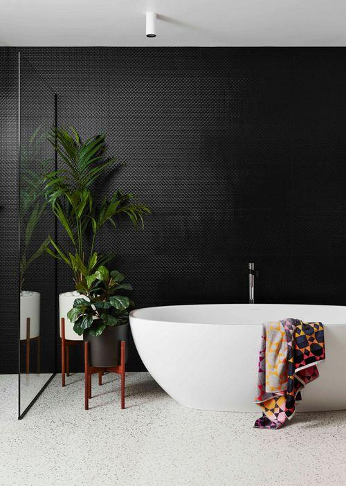 """For someone who happily declares she's """"certainly not a minimalist"""", the monochrome palette of the family bathroom was a surprisingly restrained choice by the owner. Large-scale black gloss 'Damier Noir' tiles from Signorino guarantee a dramatic feature wall in the wash zone, while a pink-and-orange 'Bunting' bath sheet from Fenton & Fenton adds a requisite splash of colour against the Victoria & Albert 'Barcelona' freestanding bath and Reece tapware. Planters from Luc Design house some lush greenery."""