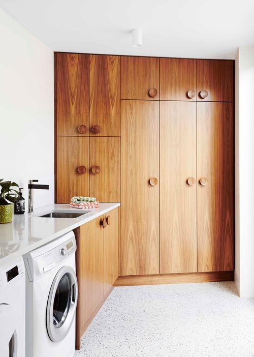 """More American walnut cabinetry, together with a Silestone benchtop in Lagoon, reigns supreme in the laundry, and helps this room feel less like a working space and more like the rest of the home. """"The round handles on the cupboards were custom-made by an 80-year-old wood turner we found in the north of Tasmania,"""" says the owner. """"It's important to pay attention to smaller items such as the handles."""""""