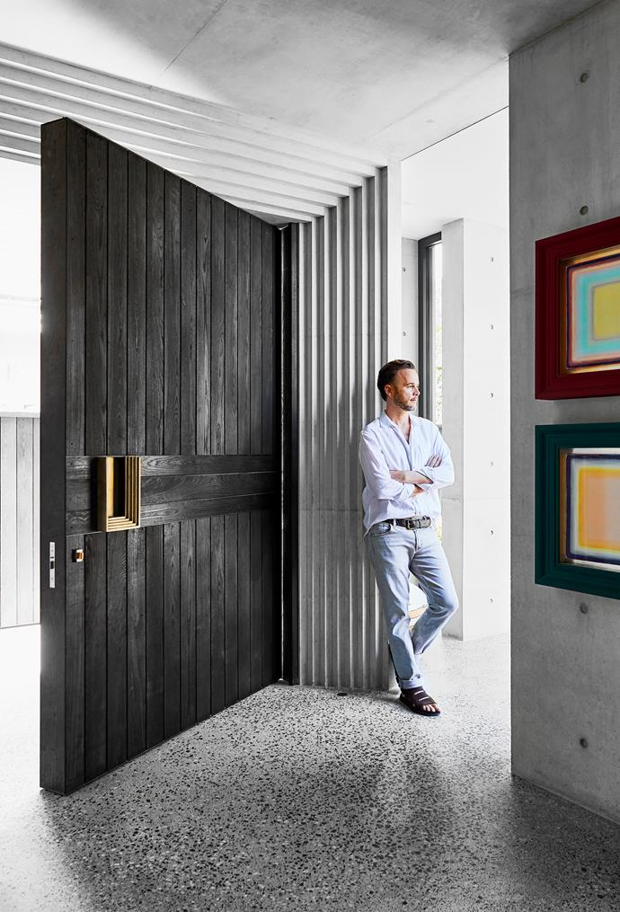 Architect Daniel Boddam by the crafted front door in Cambia ash with custom brass pull, which sits within an art deco-inspired monumental faceted doorway. Artworks by Tomislav Nikolic.