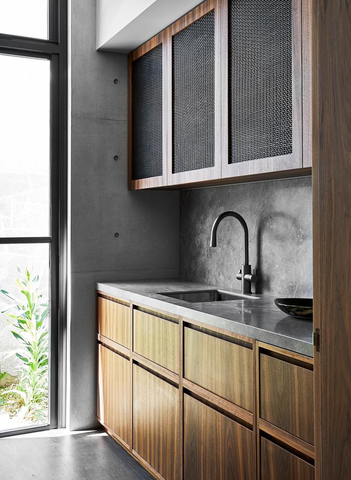 In the butler's pantry, joinery in American walnut with aged-brass mesh inserts. Benchtop in Maximum 'Fior Di Bosco' porcelain panels from Artedomus. Zip Celsius 'Arc G5' HydroTap.