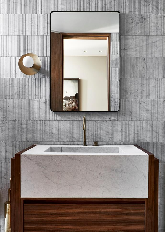In the downstairs bathroom, custom vanity by Nu Space with basin in Carrara marble from Euro Marble and Vola '590V' deck-mounted mixer in Brass. Custom mirror and 'Celeste' sconce by Daniel Boddam.