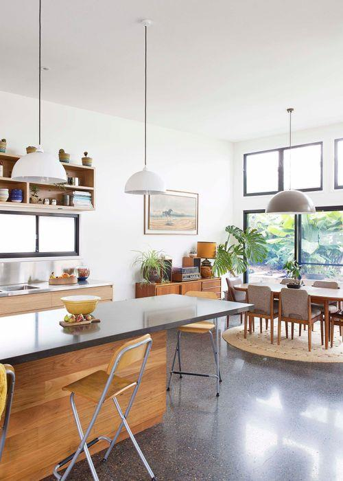 A large window behind the stainless-steel workbench brightens the cleverly designed kitchen. It is a lovely, simple space that multiple people can be in without it feeling crowded. In the centre of the zone, which adjoins the dining room, a cantilevered island bench enveloped in inky Caesarstone Raven is paired with practical 'Franklin' bar stools from Ikea. Above the bench, a grouping of bespoke aluminium pendants from Light Up Balgowlah brings further warmth to the hub of the home, as does the highly durable timber-look joinery. On the floor, a cute felted wool Muskhane 'Kali' rug from Nomades Interiors & Homewares adds a fanciful touch, along with a trio of Robert Gordon ceramic birds and a Pony Rider 'Wanderluster' wall dot.