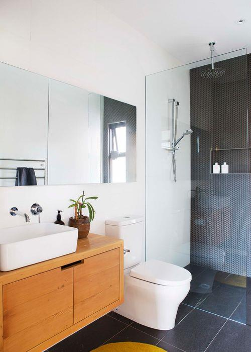 Matt white wall tiles and grey ceramic floor tiles from Amber Tiles let a statement 'Mechanics 1 Light Cage' pendant from Beacon Lighting shine. The custom-made timber vanity is teamed with a Kohler basin and a mirrored shaving cabinet, both from Harvey Norman, and a Porcher 'Cygnet' toilet suite from Reece.