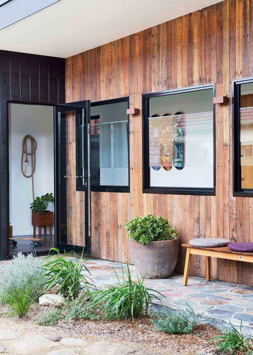 Recycled timber flooring from an old shed on the original property lines the external wall. A Big W 'Patio' bench by Jamie Durie and Muskhane 'Chakati' cushions provide a comfortable landing spot.