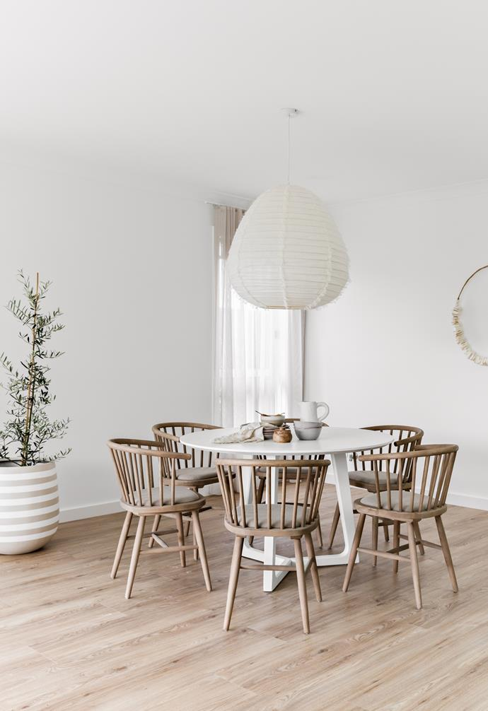 """Timber chairs, an [indoor olive tree](https://www.homestolove.com.au/potted-olive-trees-21915 target=""""_blank"""") and a large white pendant light create a c[asual and serene dining space](https://www.homestolove.com.au/relaxed-dining-area-ideas-3675 target=""""_blank"""")."""