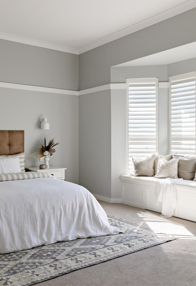 The master bedroom is an elegant space with sophisticated  space blue, grey and white tones.
