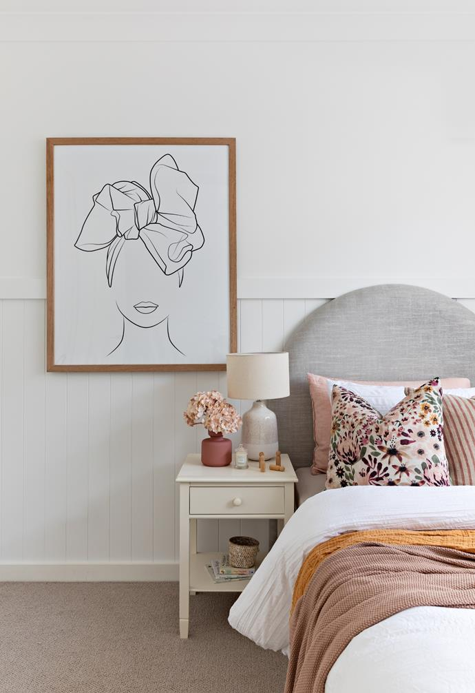 A monochrome artwork and a soft pink palette brings a feminine air to this bedroom.