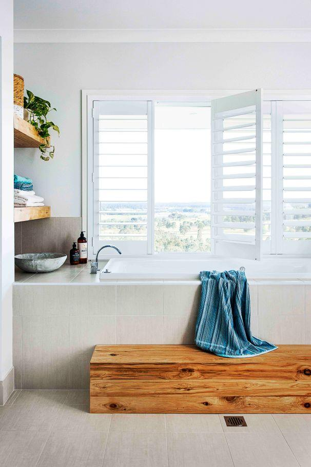**Classic with modern touches**<br><br> This built-in bath is cleverly positioned to make the most of the glorious views from the shuttered window. The simple colour palette keeps the space looking fresh while the timber furnishings add texture.