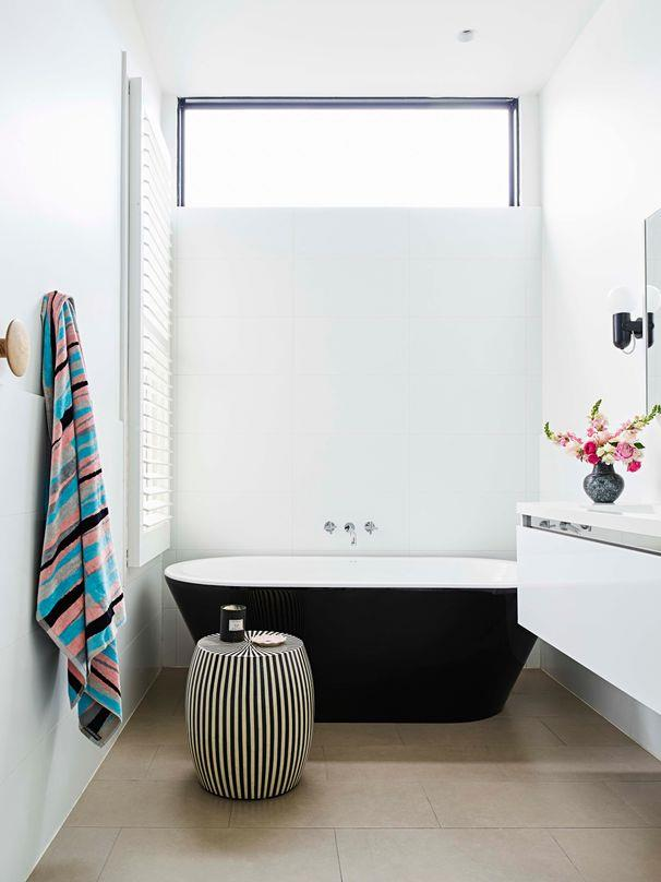 **Monochrome magic**<br><br> The simple colour palette of black and white is made ever so chic with little details, such as the striped seat, black light, dark window trim and metallic touches. Floating the vanity helps to create an illusion of space.