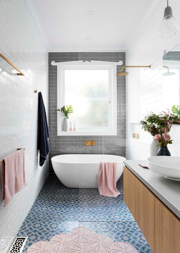 **Classic with modern touches**<br><br> This strikingly modern bathroom combines subway tiles and brass tapware, with encaustic tiles on the floor injecting personality. The pops of pink add a feminine touch to the space and help soften the overall look.