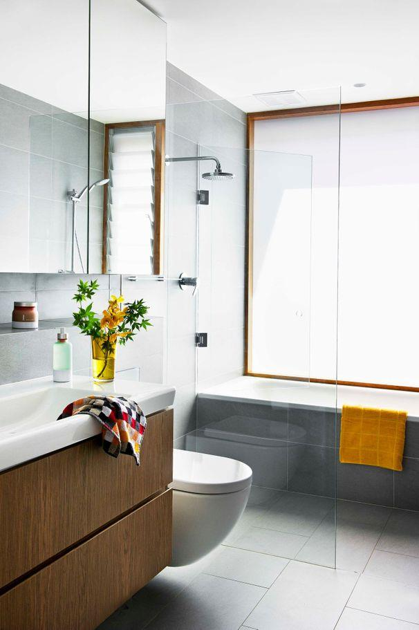**Compact space**<Br><br> A study in simplistic elegance, in this bathroom grey tiles wrap up the walls, enhancing the sense of space. Timber around the windows ties in with the vanity and adds warmth.