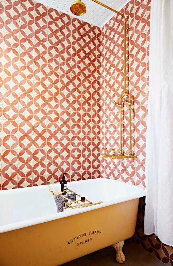 **Vintage Touch**<br><br> Playful orange tiles, a freestanding bath and exposed brass pipes create a fun, retro-style bathroom.