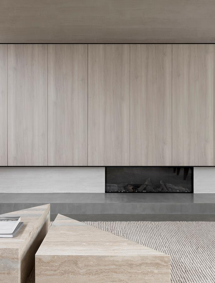 A palette of calming neutrals sets a warm scene in the living room where the 'DS1400' fireplace from Escea is set within a rendered finish by Carlier & Co and the joinery is in 'NavUrban Balmoral' panels from New Age Veneers. Travertine coffee tables by Adam Kane Architects.