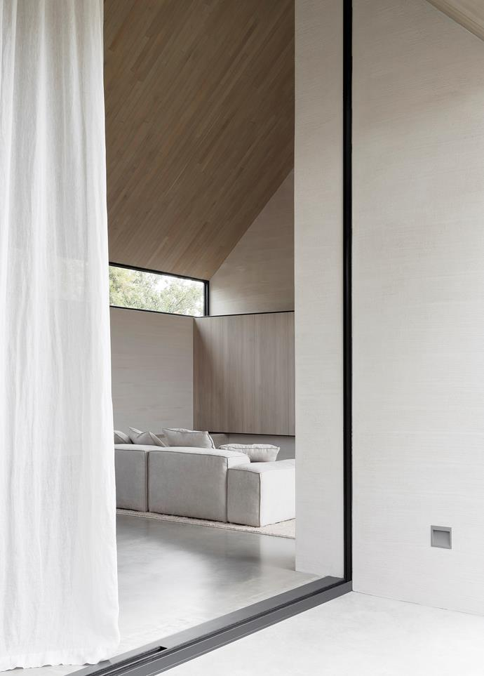 Linen sheer curtains by Lovelight filter the abundant light coming through the sliding door from All Seasons Windows and illuminate the burnished concrete floor.