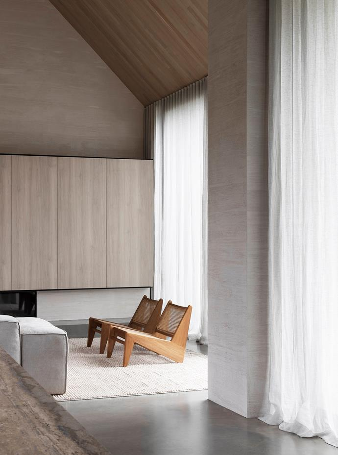 The soaring roof is clad in American oak from Made By Storey with custom stain by Scanlan & Makers. 'Elio' modular sofa from MCM House and pair of Pierre Jeanneret 'Kangaroo' armchairs from Tigmi Trading, all on a 'Malawi' rug in Oatmeal from Armadillo.
