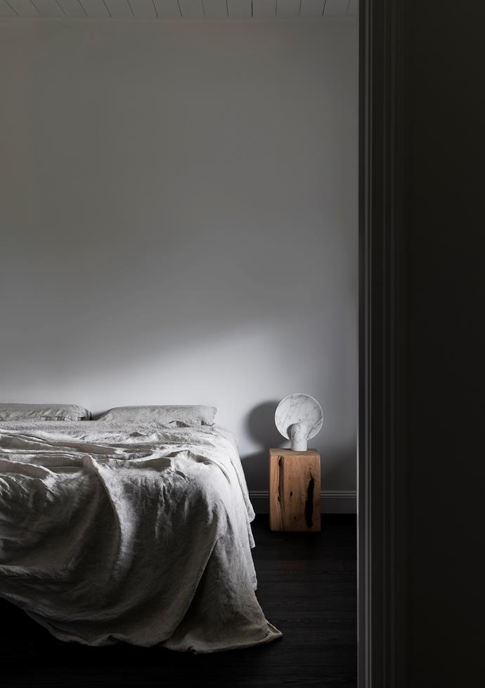 A mix of linen bedding from Bed Threads and the 'Block Stool' bedside table from Fire-Away Fire Pits add their tactile looks and natural tones to the bedroom. 'Surface Sconce' table lamp by Henry Wilson from Studio Henry Wilson. Flooring in 'Cinder' engineered oak from Made By Storey. The walls are painted in Dulux 'Lexicon'.
