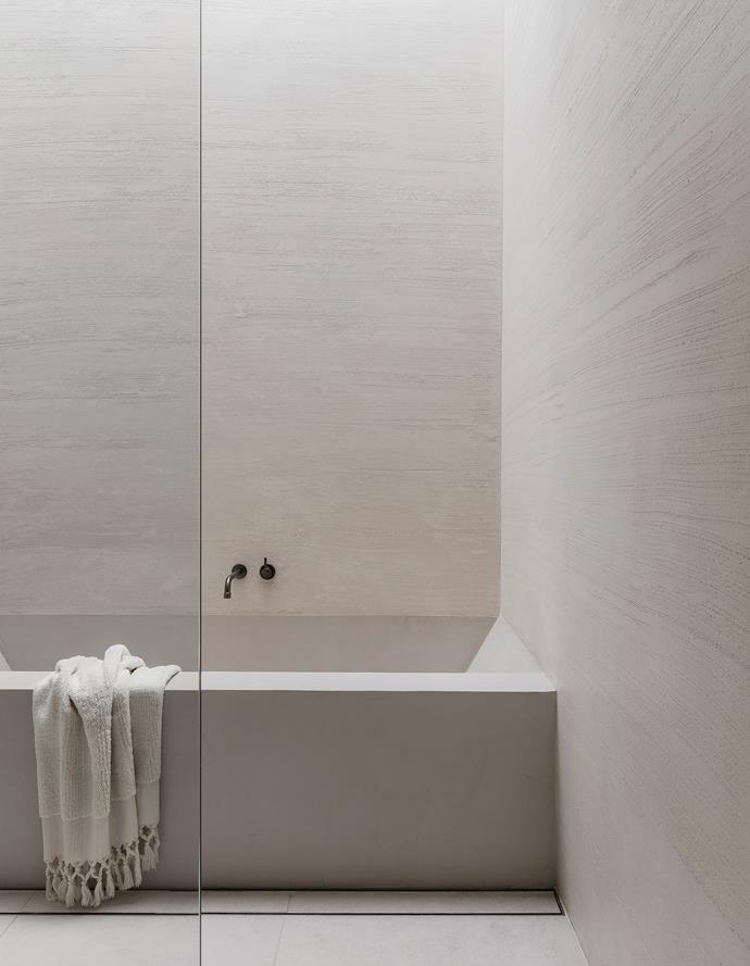 A linen bath towel from Loom Towels drapes over the custom design bath by Adam Kane Architects with finish by Carlier & Co and Brodware 'Yokato' tapware in Aged Iron. On the floor are porcelain tiles from G-Lux.