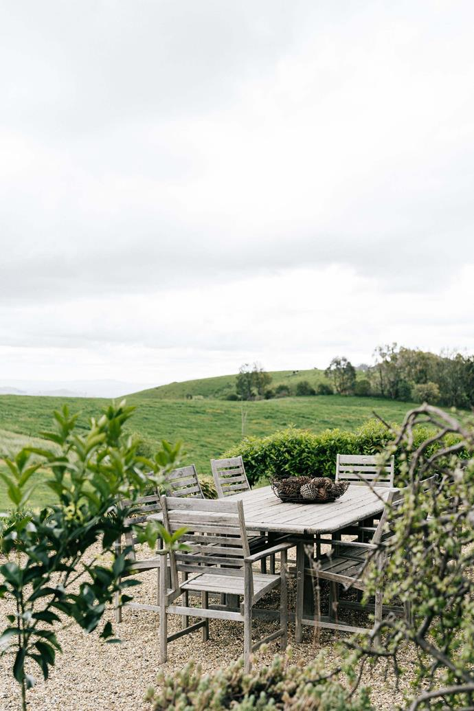 The outdoor dining area is surrounded by views of rolling hills.