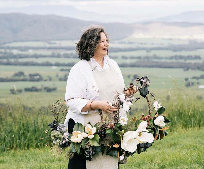 Woman holding handmade flower wreaths with green hills in the background