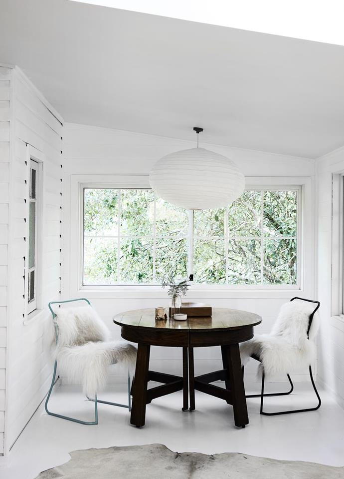 """Eames dining chairs in the sunroom with sheepskin throws and an oversized cotton pendant from The Society Inc add a wonderful white luminosity in this peaceful [Queenslander home in the Byron Bay Hinterland](https://www.homestolove.com.au/queenslander-home-byron-bay-21284 target=""""_blank"""")."""
