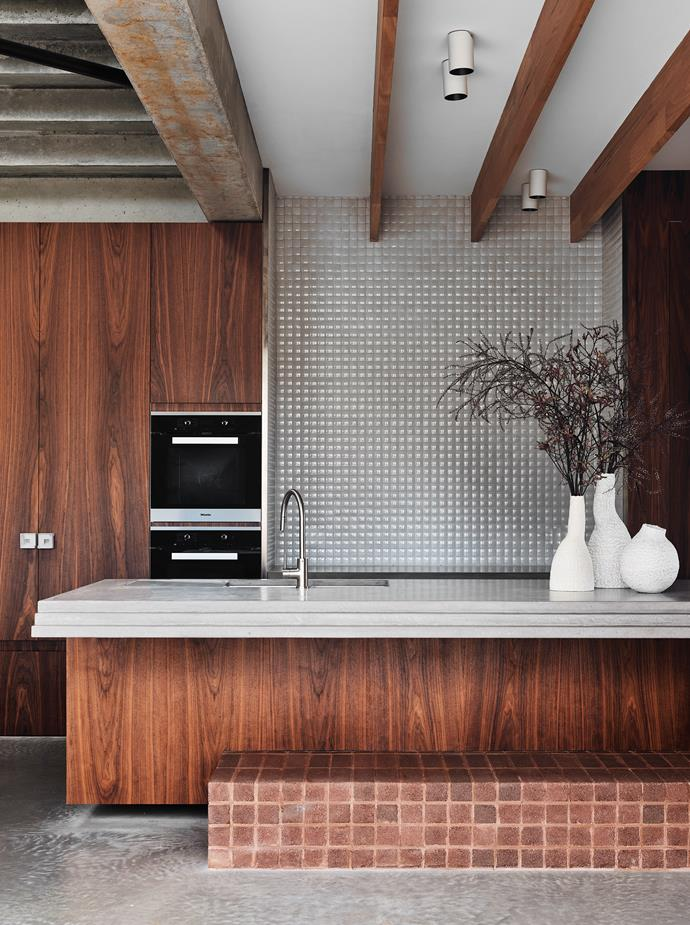Ceramics by Mark Young add a curvaceous touch on the hand-trowelled concrete bench by Concrete Collective with Brodware 'City Stik' pullout kitchen mixer. Cabinets by Esar Joinery in American walnut veneer. Inax 'Madoka' tiles on the splashback from Artedomus. Miele 'H6260BP' oven and 'KM6388' induction cooktop with Schweigen 'UMPA95' rangehood. Brightgreen 'D900 SHX' curved LED downlight.