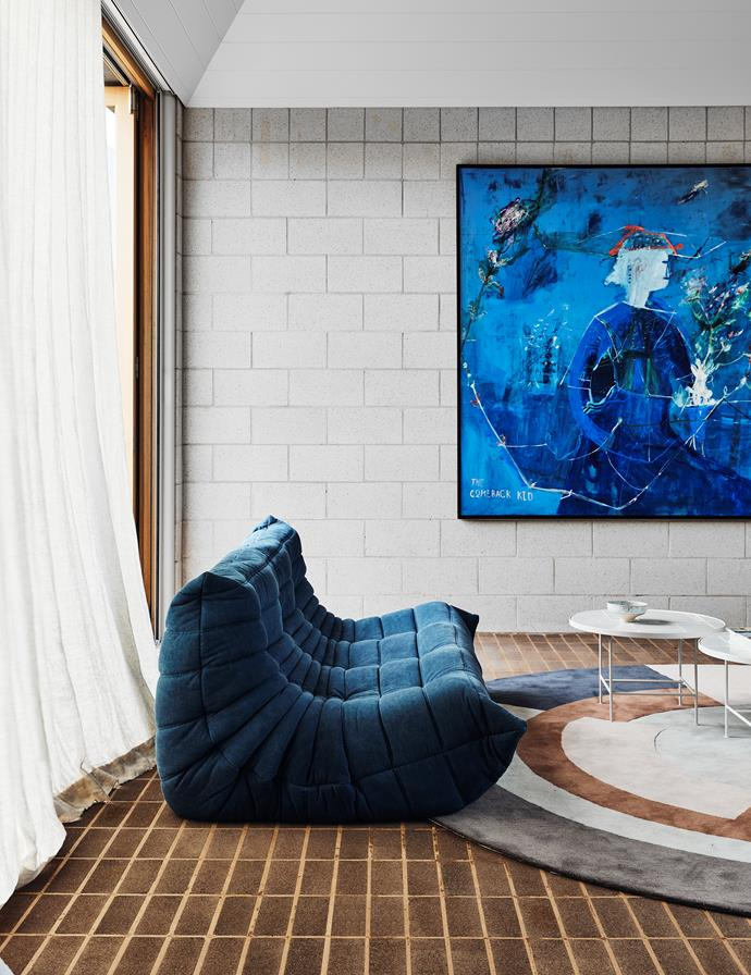 In the rumpus room, the blue tones of George Raftopoulos' artwork Comeback Kid from Studio Gallery are seen in the Ligne Roset 'Togo' three-seat sofa from Domo. 'Anchor' side table from Grazia&Co. Bernabeifreeman 'Plateau' rug from Designer Rugs. The small bowl was a gift from the client's mother.