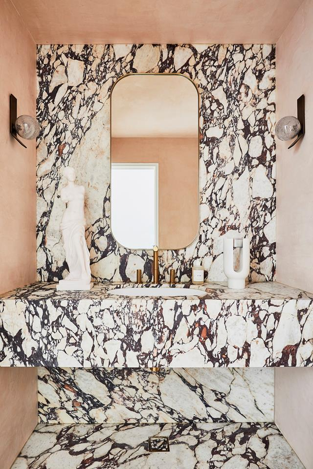 """The bold combination of Calacatta Viola marble, pink stucco walls and brass fittings and fixtures create a sense of whimsy in this striking [powder room](https://www.homestolove.com.au/new-york-style-modern-family-home-22238 target=""""_blank"""") designed by Alexandra Brown of Alexandra Brown Interiors."""