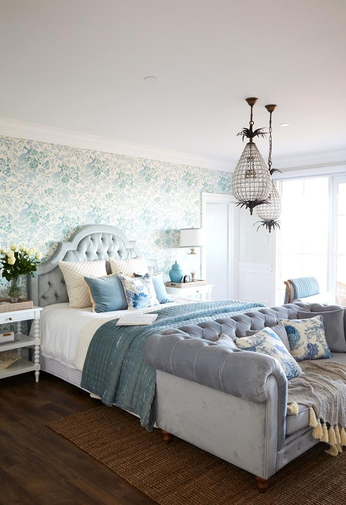 """""""I love soft colours with a crisp feel and always use duck egg blues in main bedrooms,"""" says Natalee of the serene palette in the bedroom. A delicate Peacock grasscloth wallpaper by 3Beaches in a custom colour creates a stunning backdrop for the luxurious upholstered bedhead by Indah Island. Textural layers, such as the custom cushions and a velvet throw from Her Shed, add to the feminine feel. A One World lamp paired with a St John lampshade provides perfect illumination for bedtime reading."""