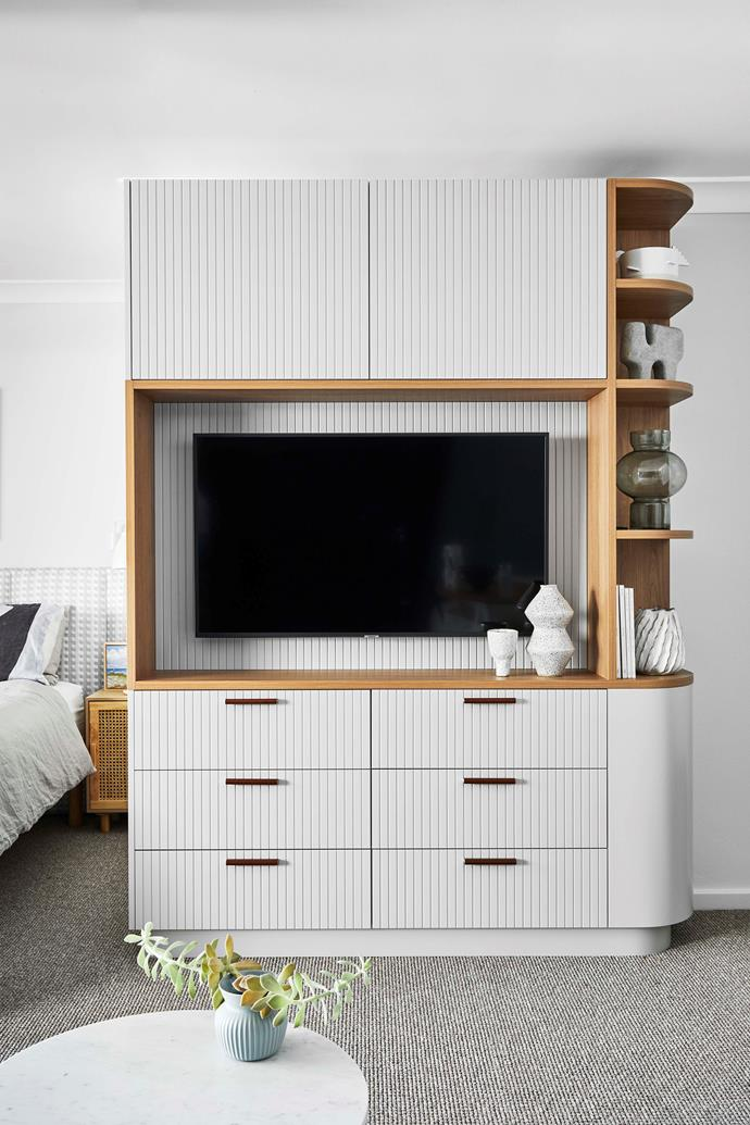 The TV unit was designed by Josie to disguise the TV and hide the bed from view when people walk into the apartment. Leather handles on the drawers add a textural touch.