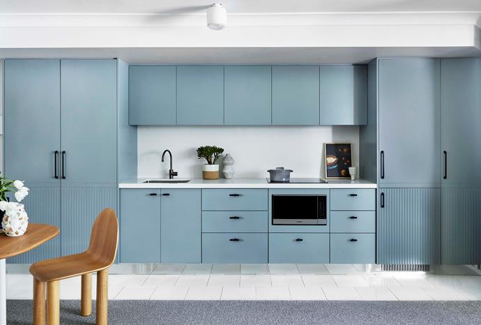 """Polyurethane drawers and cupboard fronts are Dulux Rangitikei River Half, teamed with a new benchtop and splashback in Caesarstone Organic White. """"We replaced the existing [mirrored splashback](https://www.homestolove.com.au/splashback-finishes-4432 target=""""_blank"""") because you can already see everything in this space, and I didn't think we needed to reflect the bed into the kitchen,"""" says interior designer Josie Simpson of Altus Design Studio."""