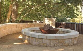 Metal backyard fire pit surrounded by sandstone wall