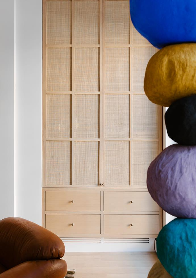 The vibrant Annie Morris sculpture and Gianfranco Frattini 'Sesann' vintage leather armchair frame the outlook through to the raffia-clad joinery.