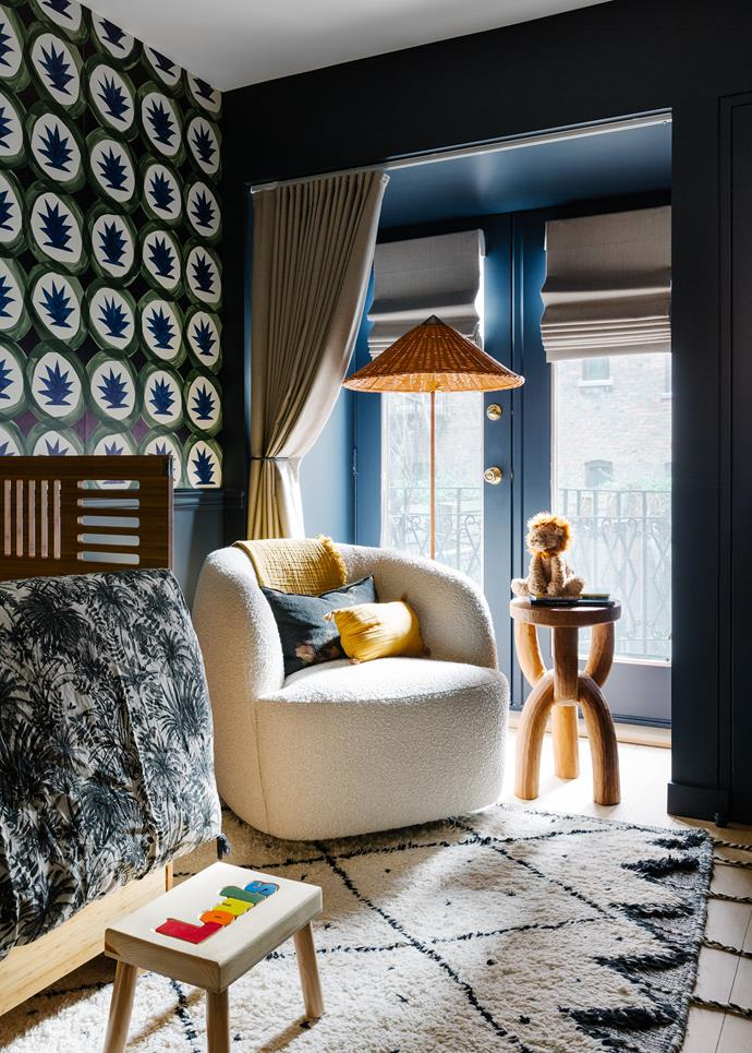 Louis's bedroom is papered in Hermès 'Dune' wallpaper and painted in Clare 'Goodnight Moon'. CB2 'Gwyneth' bouclé chair, Kalon crib and Gubi '9602' bamboo floor lamp. Carved 'Chain' stool from Jayson Home. Vintage Moroccan rug.