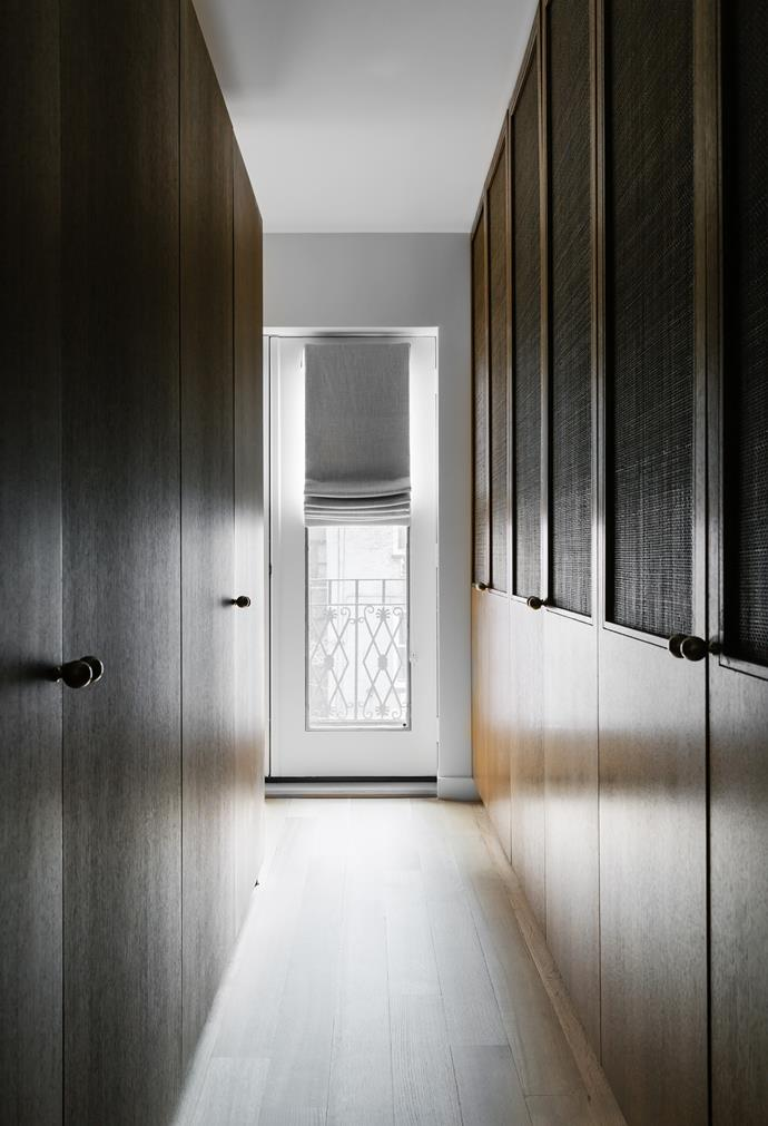 The master bedroom walk-in robe offers abundant concealed storage. The wardrobes were designed by Tali and made in oak stained in an espresso finish with inset raffia panels.