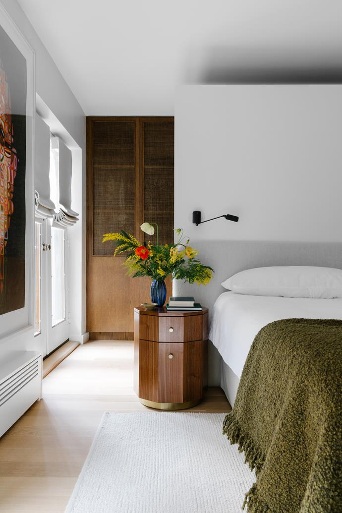 A custom bedhead in beige bouclé has been integrated into a wall panel near ceiling height that creates an airiness and serves to separate the sleeping quarters from the walk-in robe and its back row of closets. Tom Dixon bouclé bed throw in Khaki. 'Quillen' marquetry bedside table from Anthropologie. A Chuck Close artwork hangs near the windows, which are shaded with wool blinds. 'Palermo' rug in Bone from Armadillo.