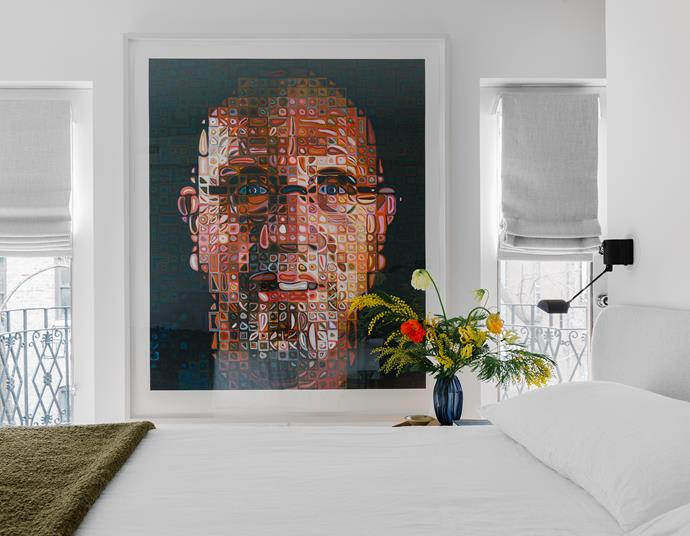 An attention-grabbing portait by New York artist Chuck Close hangs near the master bedroom windows which are shaded with wool blinds. Tom Dixon khaki bouclé bed throw.