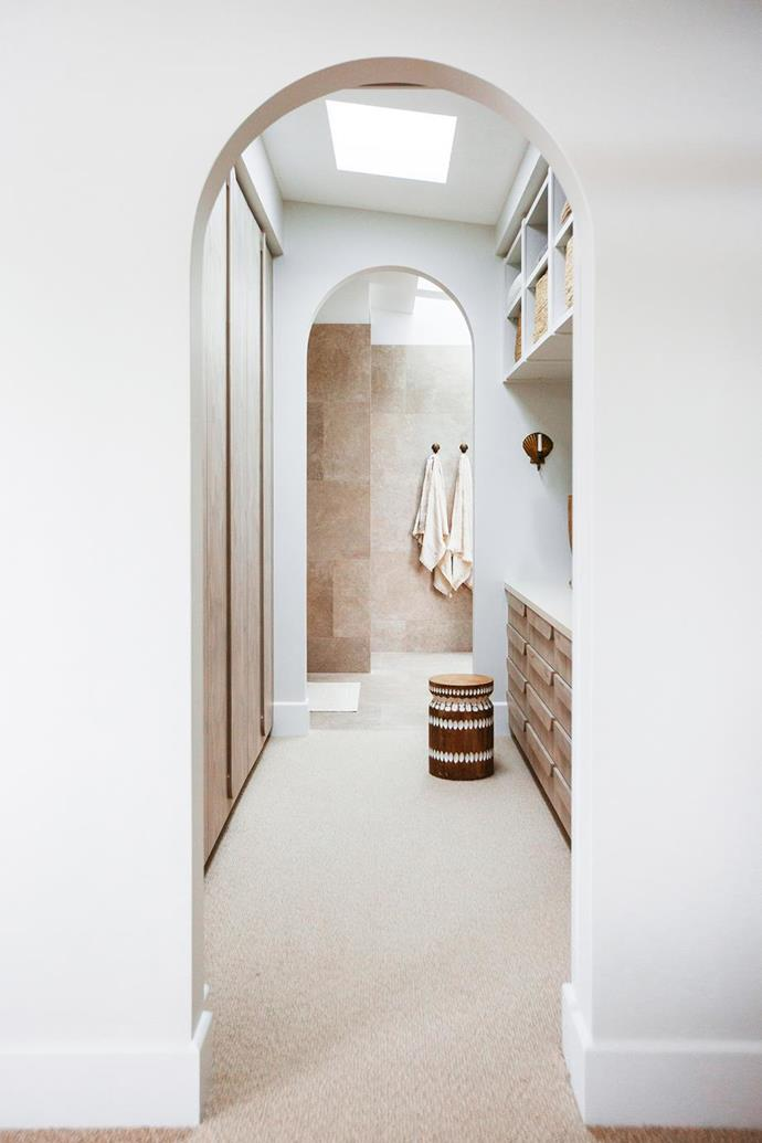 """The two arch doorways make a design feature of the walk-in robe and ensuite zones, leading to a travertine encased ensuite in [Kyal and Kara's Mediterranean-style home](https://www.homestolove.com.au/kyal-and-kara-new-home-21483
